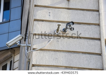 Security camera on the wall of a house - stock photo