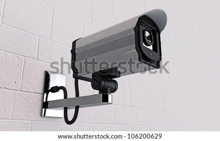 security camera on tiled wall - stock photo