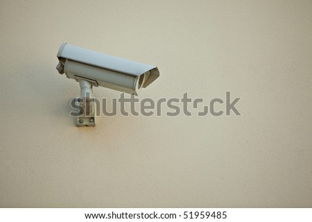 Security camera on wall of modern building - stock photo