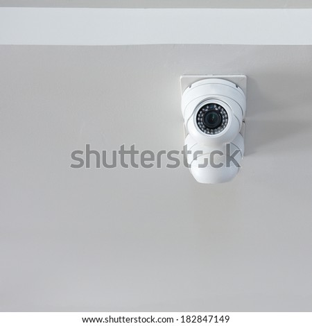 security camera on white wall in the office, cctv in home - stock photo