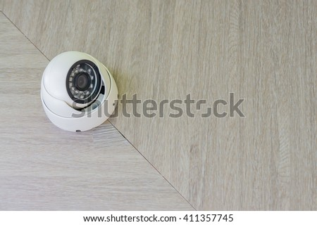 security camera on wooden ceiling background - stock photo