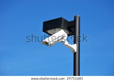Security camera placed in a street lamp. - stock photo