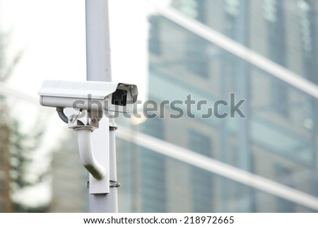 Security camera system on a pole guarding business building - stock photo