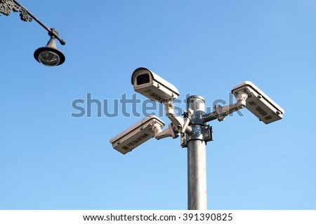 Security cameras against blue sky