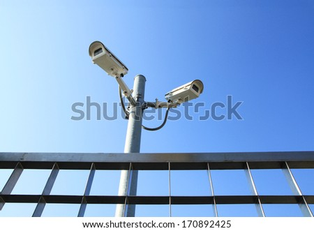 Security cameras and metal fence - stock photo