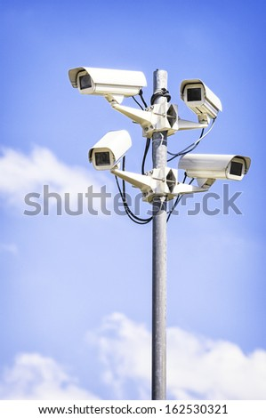 security cameras in front of blue sky - with space for text