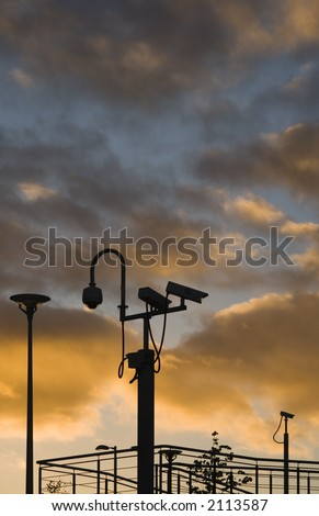 Security cameras silhouetted against an evening sky - stock photo
