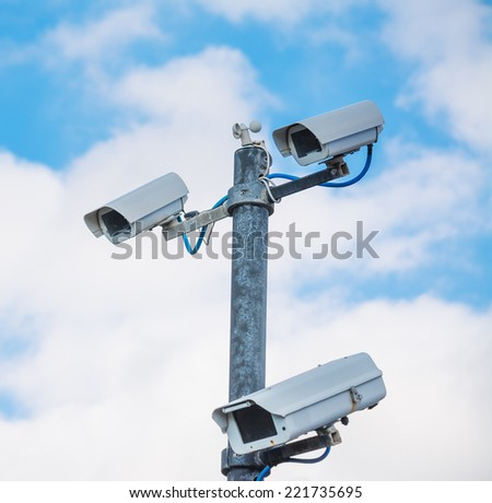 security cameras under a cloudy sky - stock photo