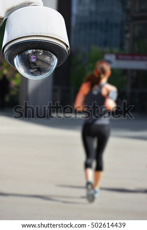 security CCTV camera or surveillance system with jogger on blurry background