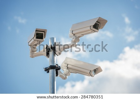 Security cctv surveillance camera in front of blue sky concept for counter-terrorism, antiterrorism and protection from crime - stock photo