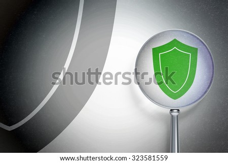 Security concept: magnifying optical glass with Shield icon on digital background, empty copyspace for card, text, advertising - stock photo