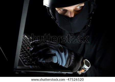 Security concept with dangerous man thief and laptop at night, internet crime online - stock photo