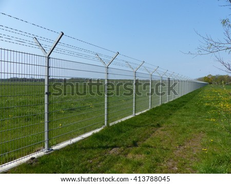Security fence of an international airport - stock photo