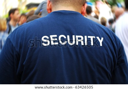 security guard in front of blurred crowd - stock photo