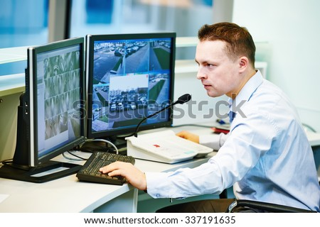security guard officer watching video monitoring surveillance security system - stock photo