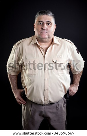 Security guard portrait, on a black background.  - stock photo