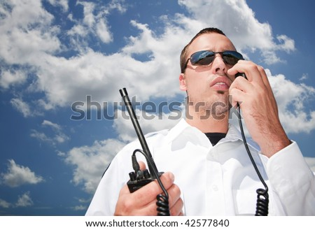 Security guard using hand-held radio for communication - stock photo