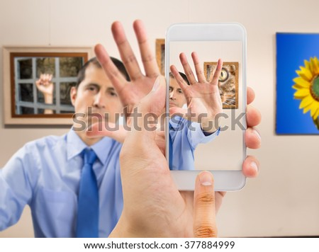 security guard with arm raised and open palm gesturing forbidding to take photos at the museum gallery with pictures of my property in background - stock photo