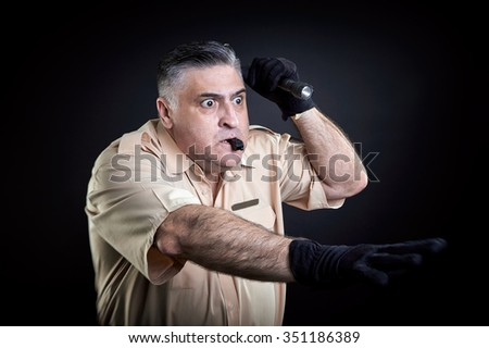 Security guard with flashlight, making the stop sign. Black background. - stock photo