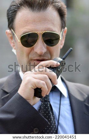 Security guard with glasses and walkie-talkie in his hand, FOCUS ON THE HAND - stock photo