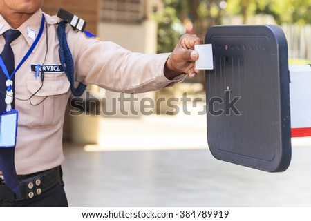 Security guard with opening barrier gate - stock photo