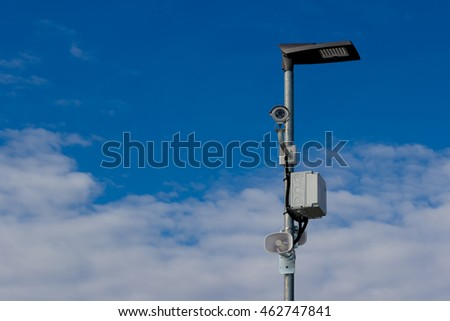 Security (industrial) camera (CCTV) on the street lamp pillar with tannoy (amplifier).