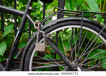 Security lock and chain blocking the bicycle wheel in a park