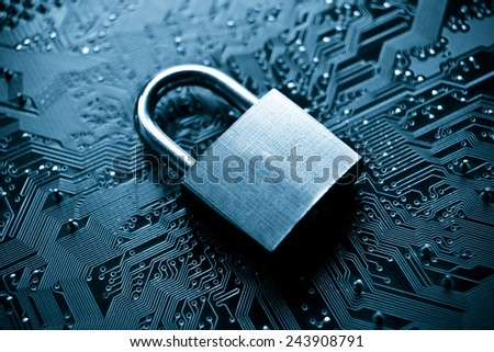 security lock on computer circuit board - computer security concept - stock photo