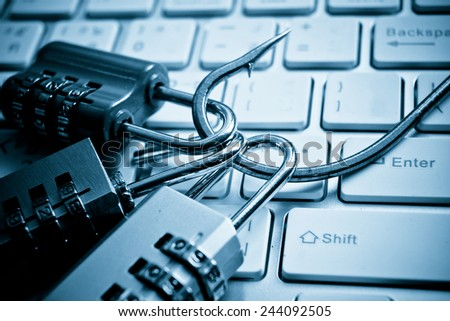 security locks with a fish hook on computer keyboard / security breach concept / phishing