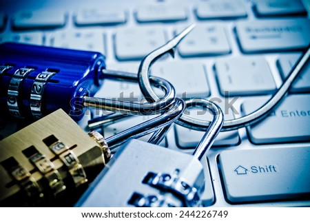 security locks with a fish hook on computer keyboard / security breach concept / phishing - stock photo