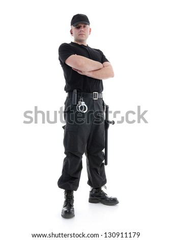 Security man wearing black uniform equipped with police club and handcuffs standing confidently with arms crossed, shot on white - stock photo