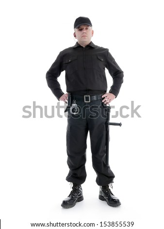 Security man wearing black uniform equipped with police club and handcuffs standing confidently with hands resting on hip , shot on white - stock photo