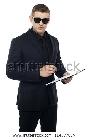 Security officer writing on clipboard while looking at you - stock photo