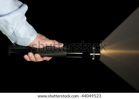 Security or law enforcement holding a flashlight in the dark - stock photo
