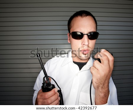 Security Patrol office holding radio with handset - stock photo
