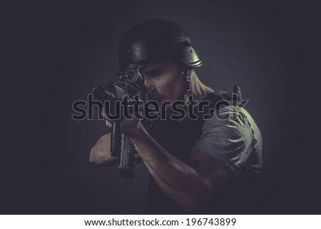 Security  sport player wearing protective helmet aiming pistol ,black armor and machine gun - stock photo