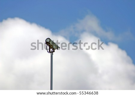 Security / surveillance camera against a cloudy sky - stock photo