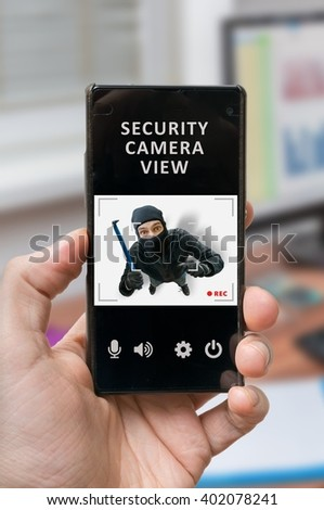 Security system concept. Man holds smartphone with security camera view on thief or robber. Security alarm is recording burglar. - stock photo