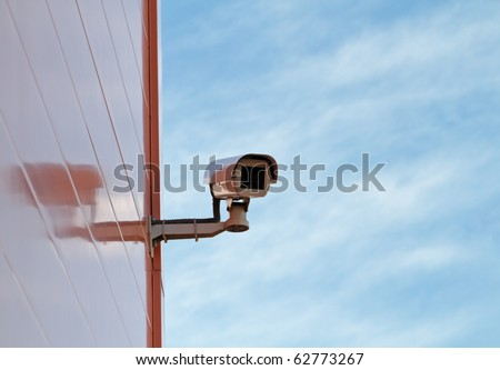 security video camera and blue cloudy sky - stock photo