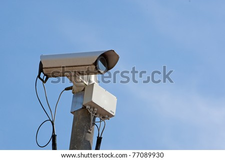Securitycamera against blue sky - stock photo