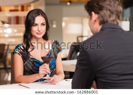 Seducing beautiful woman looking at her lover with wine glass. Having romantic talk  - stock photo