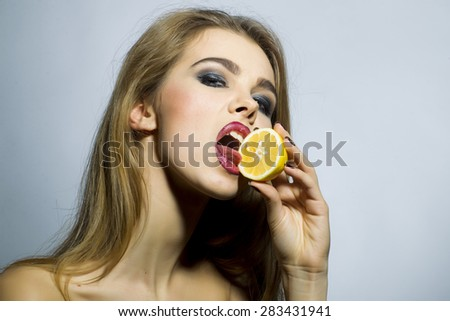 Seducing blonde woman portrait with bright make up looking forward holding half of fresh juicy orange standing on gray background copyspace, horizontal picture - stock photo