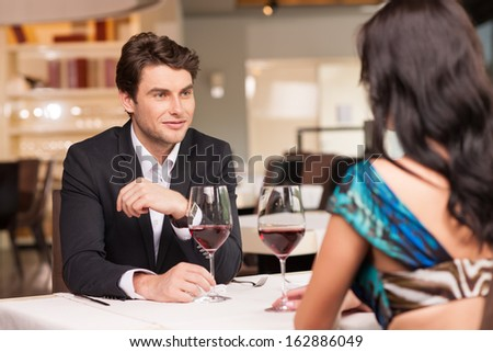 Seducing  handsome man looking at beautiful dark hair woman with wine glasses. Romantic and love mood  - stock photo