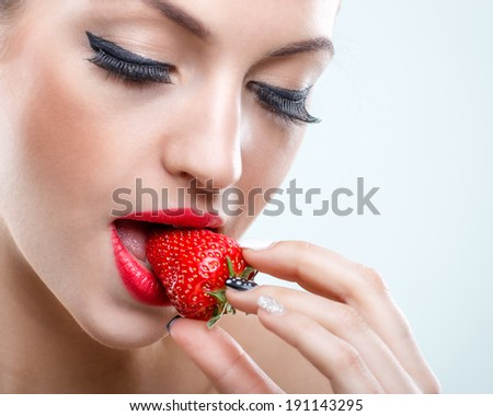 Seduction - Beautiful woman when closed eyes, take a bite of the strawberry - stock photo