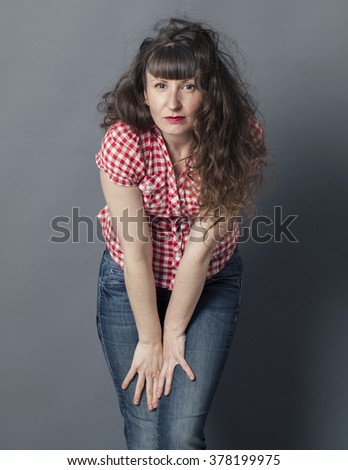 seduction concept - portrait of a sexy natural young woman with long curly hair leaning forward to camera, gray background studio