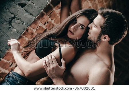 Seductive and beautiful. Handsome young shirtless man pulling down bra strap of his beautiful girlfriend while both standing near brick wall