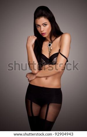Seductive beautiful woman in black lingerie and stockings, three quarter pose facing camera. - stock photo
