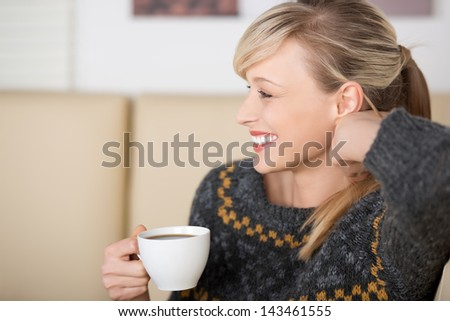 Seductive blond woman smiling and playing with her hair while drinking a cup of coffee - stock photo