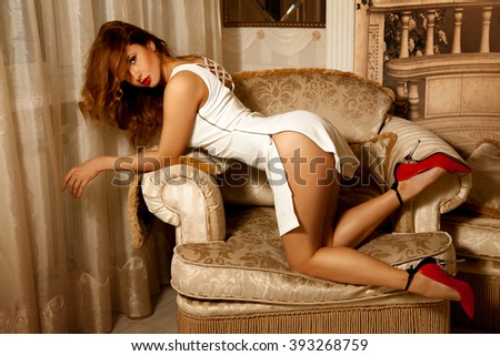 Seductive brunette woman in doggy style pose on chair. Seductive woman. Sexual woman. the concept of seduction, pleasure and desire - stock photo
