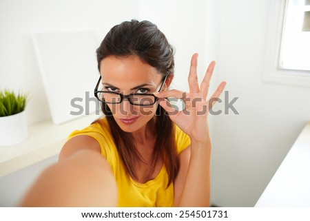Seductive brunette woman wearing glasses and chatting on her phone - stock photo